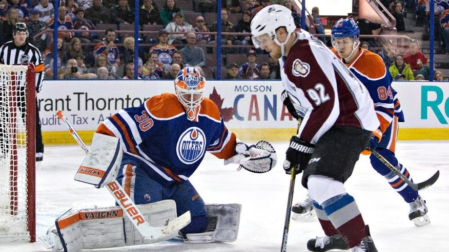 Colorado Avalanche's Gabriel Landeskog (92) is stopped by Edmonton Oilers goalie Ben Scrivens (30) as Oscar Klefbom (84) defends during the first period of an NHL hockey game Wednesday, March 25, 2015, in Edmonton, Alberta. (AP Photo/The Canadian Press, Jason Franson)
