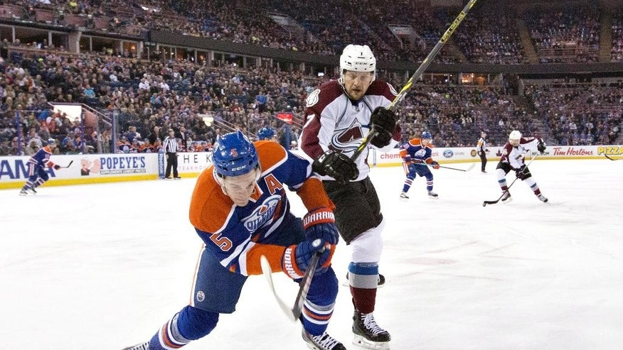 Colorado Avalanche's John Mitchell (7) checks Edmonton Oilers' Mark Fayne (5) during the first period of an NHL hockey game Wednesday, March 25, 2015, in Edmonton, Alberta. (AP Photo/The Canadian Press, Jason Franson)