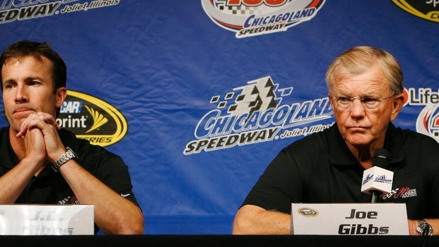 "FILE - In this July 12, 2008, file photo, Joe Gibbs, right, owner of Joe Gibbs Racing, and J.D. Gibbs, team president, talk at a press conference at Chicagoland Speedway in Joliet, Ill.  Joe Gibbs Racing President J.D. Gibbs is undergoing treatment for ""symptoms impacting areas of brain function."" The 46-year-old Gibbs is the oldest son of team owner Joe Gibbs, the Hall of Fame coach who won three Super Bowls with Washington. The team said in a statement on Wednesday, March 25, 2015,  that J.D. Gibbs has undergone a series of tests since experiencing ""speech and processing issues."" (AP Photo/Nam Y. Huh, File)"