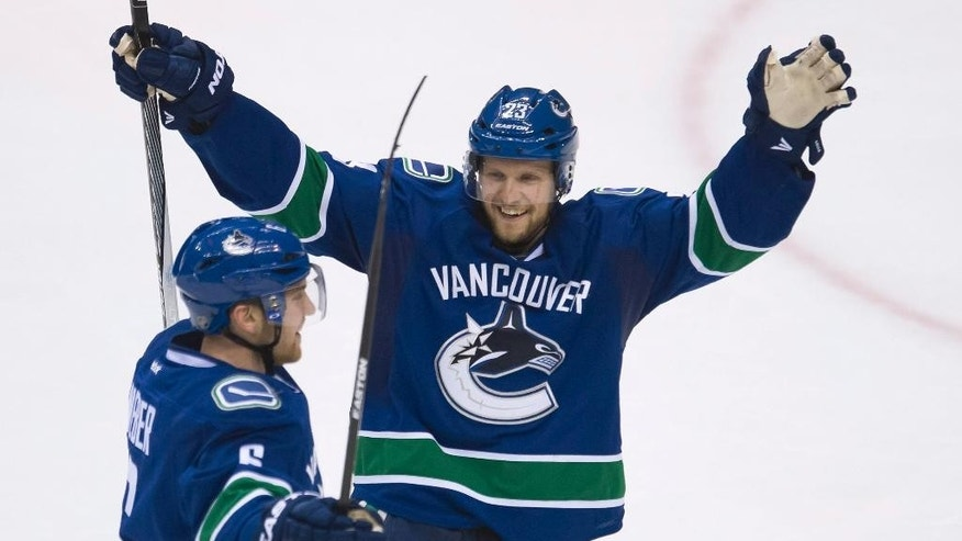 Vancouver Canucks' Yannick Weber (6) celebrates his goal against the Winnipeg Jets with teammate Alexander Edler (23) during the second period of an NHL hockey game Tuesday, March 24, 2015, in Vancouver, British Columbia. (AP Photo/The Canadian Press, Jonathan Hayward)