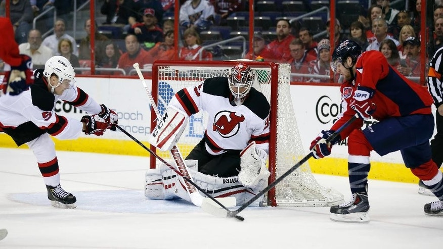 Washington Capitals right wing Tom Wilson (43) works the puck in front of New Jersey Devils goalie Cory Schneider (35) as defenseman Adam Larsson (5), from Sweden, defends, in the first period of an NHL hockey game Thursday, March 26, 2015, in Washington. (AP Photo/Alex Brandon)