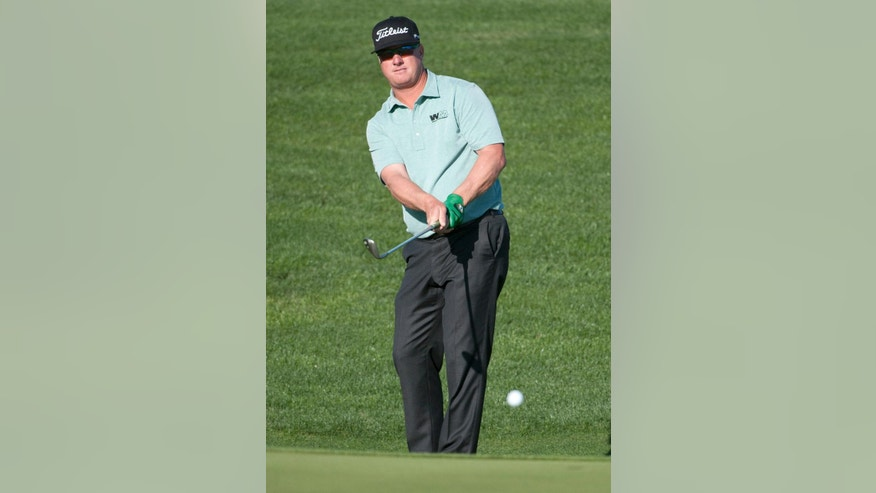 Charley Hoffman chips onto the fifteenth green during the first round of the Valero Texas Open golf tournament, Thursday, March 26, 2015, in San Antonio. (AP Photo/Darren Abate)