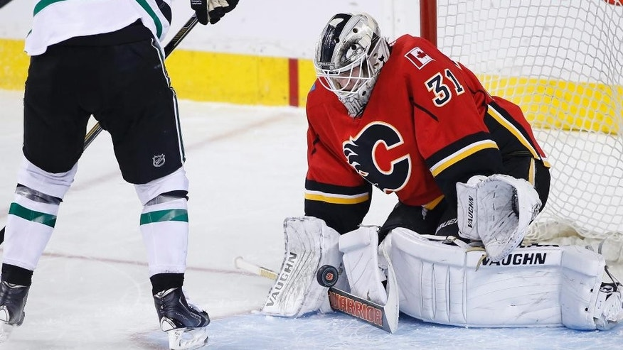 Calgary Flames goalie Karri Ramo, right, from Finland, makes a stop against Dallas Stars' Jamie Benn during the first period of an NHL hockey game Wednesday, March 25, 2015, in Calgary, Alberta. (AP Photo/The Canadian Press, Larry MacDougal)