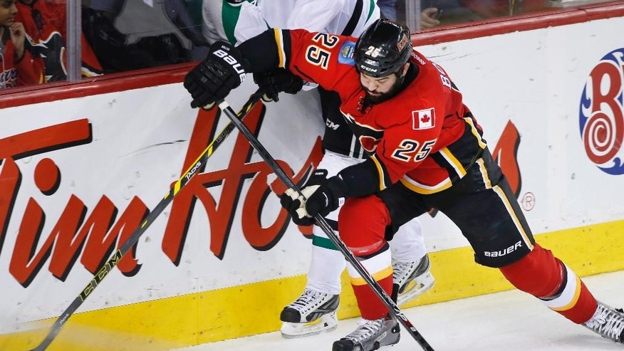Dallas Stars' John Klingberg, left, from Sweden, is hit by Calgary Flames' Brandon Bollig during the first period of an NHL hockey game Wednesday, March 25, 2015, in Calgary, Alberta. (AP Photo/The Canadian Press, Larry MacDougal)