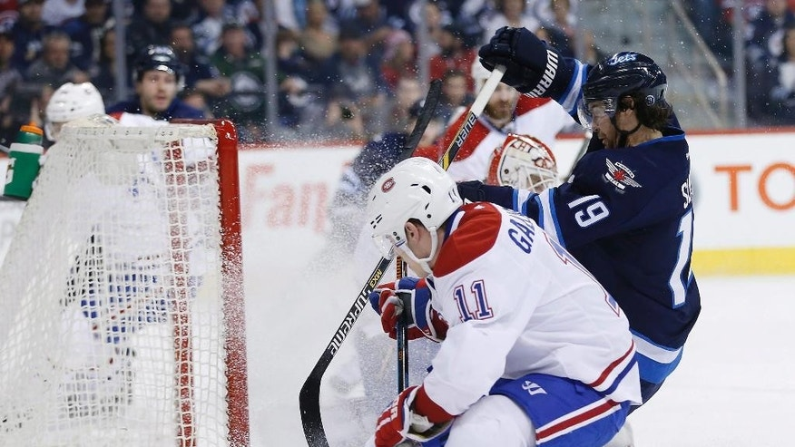 Winnipeg Jets' Jim Slater (19) scores on Montreal Canadiens goaltender Dustin Tokarski (35) as Brendan Gallagher (11) defends during the second period of an NHL hockey game, Thursday, March 26, 2015 in Winnipeg, Manitoba.  (AP Photo/The Canadian Press, John Woods)