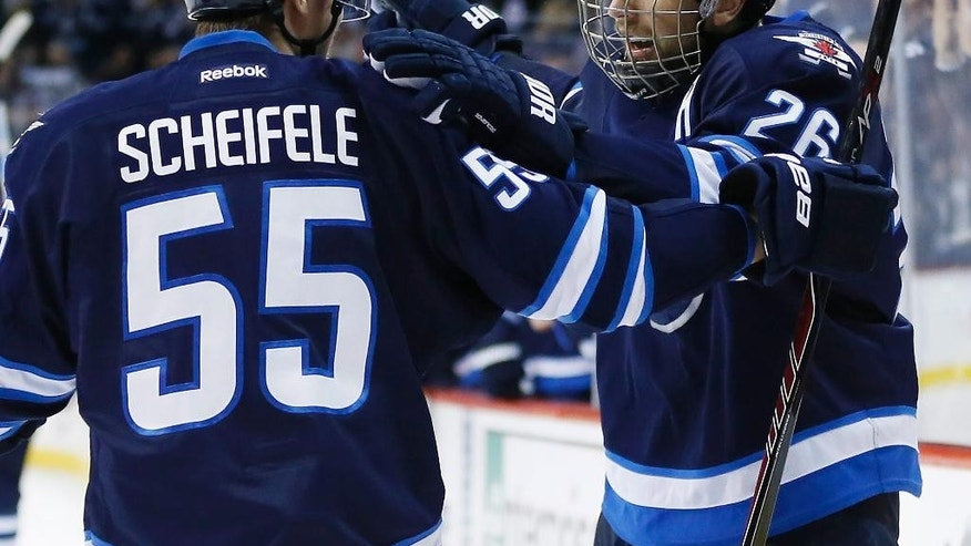 Winnipeg Jets' Mark Scheifele (55) and Blake Wheeler (26) celebrate Wheeler's goal against the Montreal Canadiens during the second period of an NHL hockey game, Thursday, March 26, 2015 in Winnipeg, Manitoba.  (AP Photo/The Canadian Press, John Woods)