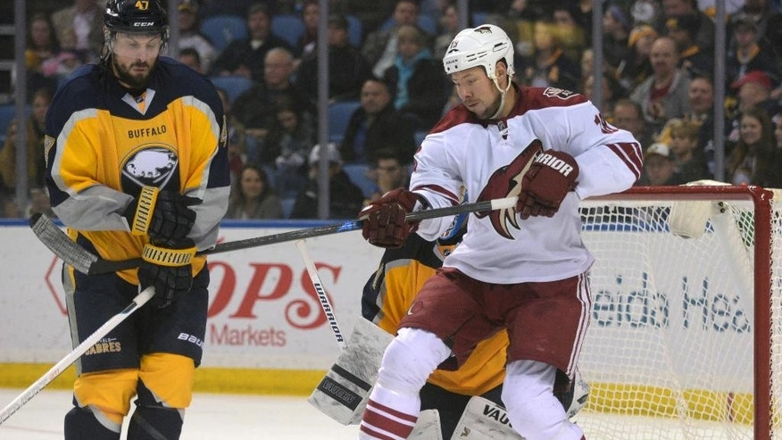 Buffalo Sabres defenseman Zach Bogosian, left, blocks a shot while Arizona Coyotes right wing David Moss (18) looks for a rebound during the second period of an NHL hockey game Thursday, March 26, 2015, in Buffalo, N.Y. (AP Photo/Gary Wiepert)