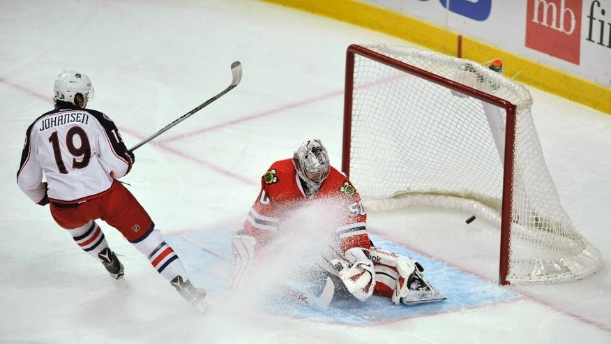 Columbus Blue Jackets' Ryan Johansen (19), scores a goal against Chicago Blackhawks goalie Corey Crawford (50) during the first period of an NHL hockey game Friday, March 27, 2015, in Chicago.  (AP Photo/Paul Beaty)