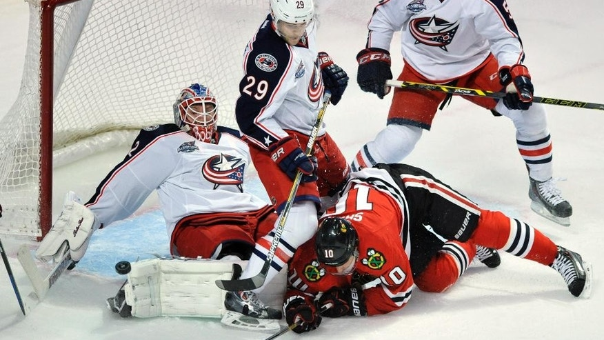 Columbus Blue Jackets goalie Sergei Bobrovsky (72) of Russia, makes a save against Chicago Blackhawks' Patrick Sharp (10), while teammates Cody Goloubef (29), and Mark Dano (56) of Austria, look on during the first period of an NHL hockey game Friday, March 27, 2015, in Chicago. (AP Photo/Paul Beaty)