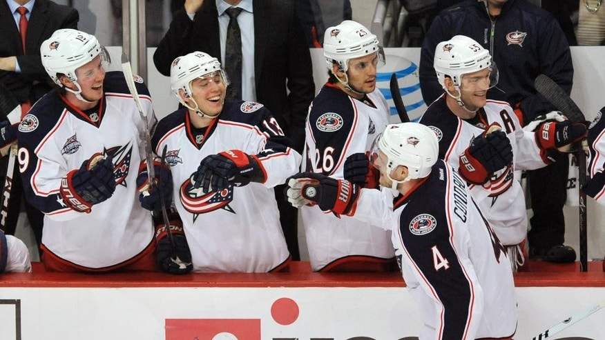 Columbus Blue Jackets' Kevin Connauton (4) celebrates with teammates on the bench after scoring during the first period of an NHL hockey game against the Chicago Blackhawks on Friday, March 27, 2015, in Chicago. (AP Photo/Paul Beaty)