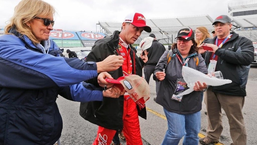 Sprint Cup driver Kevin Harvick, second from left, signs autographs after practice at Martinsville Speedway in Martinsville, Va., Friday, March 27, 2015. Rain delayed the practice and qualifying for Sunday's STP 500 Sprint Cup race.  (AP Photo/Steve Helber)