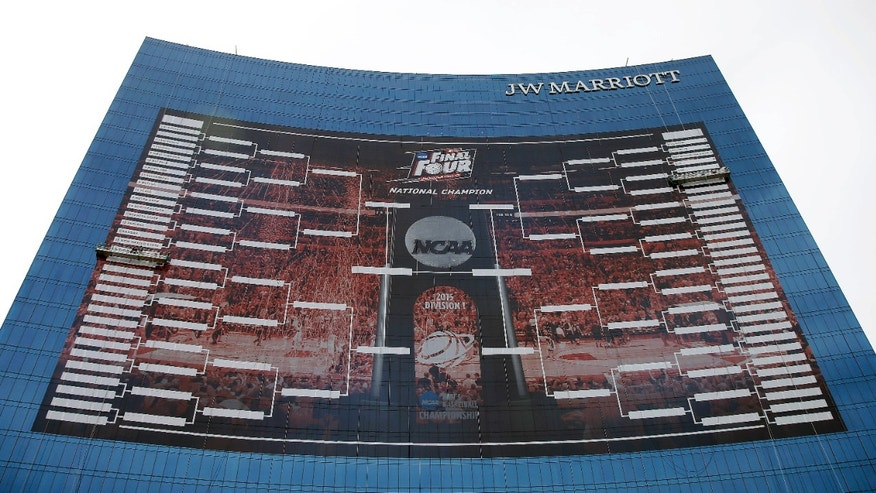 March 16, 2015: Workers add team names to a 2015 NCAA Division I men's basketball tournament bracket that is displayed on the side of the JW Marriott in Indianapolis.
