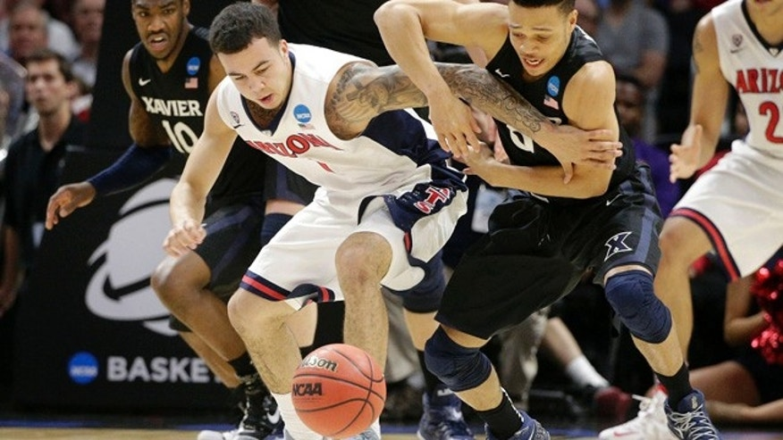 March 26, 2015: Arizona guard Gabe York, center left, and Xavier guard Larry Austin Jr. battle for a loose ball during the second half of a college basketball regional semifinal in the NCAA Tournament in Los Angeles. (AP Photo/Jae C. Hong)
