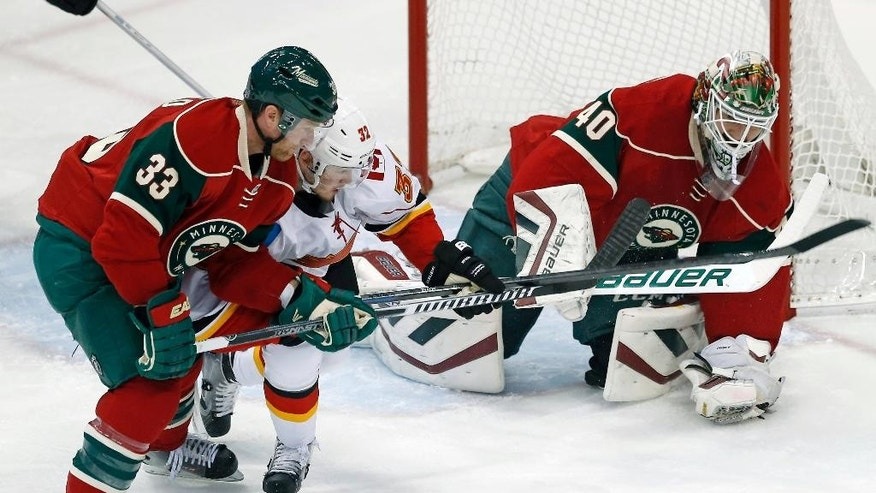 Minnesota Wild's Jordan Leopold, left, tries to keep Calgary Flames' Paul Byron from the rebound of a blocked shot by goalie Devan Dubnyk in the first period of an NHL hockey game, Friday, March 27, 2015, in St. Paul, Minn. (AP Photo/Jim Mone)