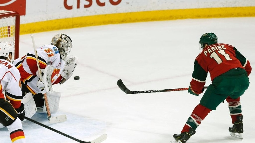 Calgary Flames goalie Karri Ramo, left, of Finland, stops a shot by Minnesota Wild's Zach Parise, right, in the first period of an NHL hockey game, Friday, March 27, 2015, in St. Paul, Minn. (AP Photo/Jim Mone)