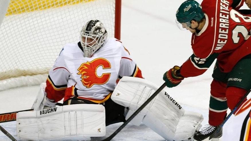 Calgary Flames goalie Karri Ramo, left, of Finland, stops a shot by Minnesota Wild's Nino Niederreiter, of Switzerland, in the first period of an NHL hockey game, Friday, March 27, 2015, in St. Paul, Minn. (AP Photo/Jim Mone)