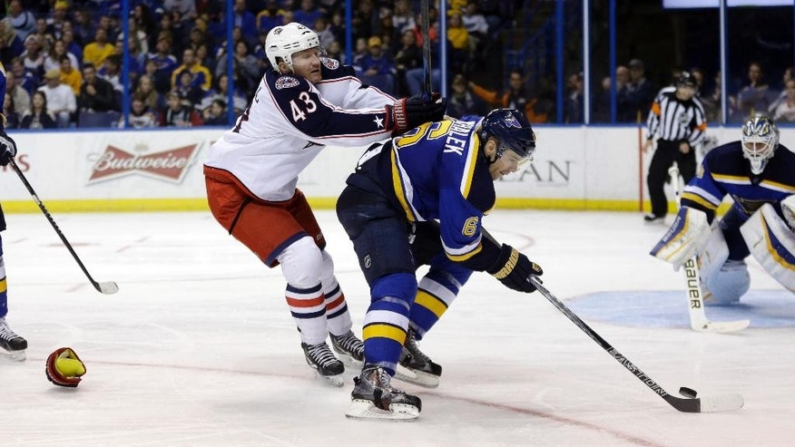 Columbus Blue Jackets' Scott Hartnell, left, loses a glove as he pushes St. Louis Blues' Zbynek Michalek, of the Czech Republic, during the third period of an NHL hockey game Saturday, March 28, 2015, in St. Louis. The Blue Jackets won 4-2. (AP Photo/Jeff Roberson)