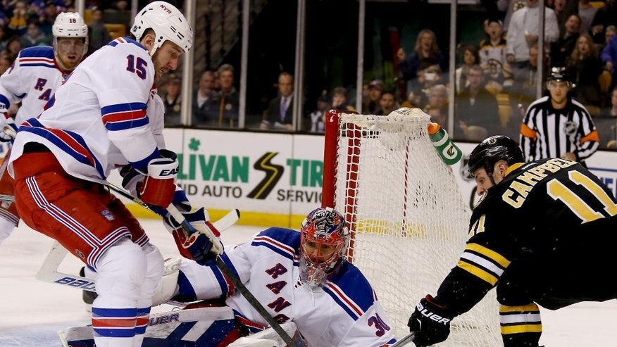 New York Rangers goalie Henrik Lundqvist (30) slides to make a save as teammate Tanner Glass (15) looks to clear the puck from Boston Bruins center Gregory Campbell (11) during the second period of an NHL hockey game, Saturday, March 28, 2015, in Boston. (AP Photo/Mary Schwalm)