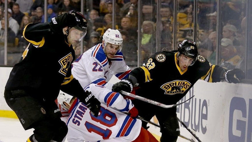 Boston Bruins center Carl Soderberg (34) and left wing Brad Marchand (63) pursue the puck as New York Rangers defenseman Marc Staal (18) falls ahead of teammate Dan Boyle (22) during the second period of an NHL hockey game, Saturday, March 28, 2015, in Boston. (AP Photo/Mary Schwalm)