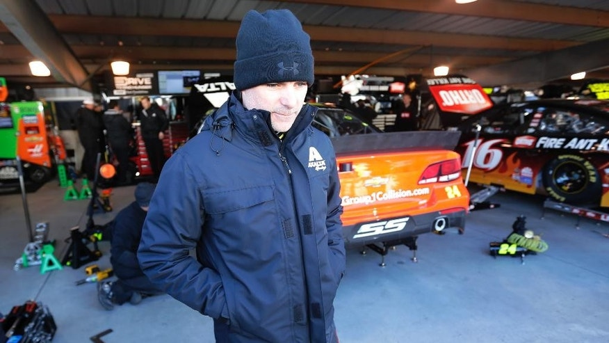 Driver Jeff Gordon is bundled up for the cold as he leaves the garage after practice for Sunday's NASCAR Sprint Cup race at the Martinsville Speedway in Martinsville, Va., Saturday, March 28, 2015.  (AP Photo/Steve Helber)