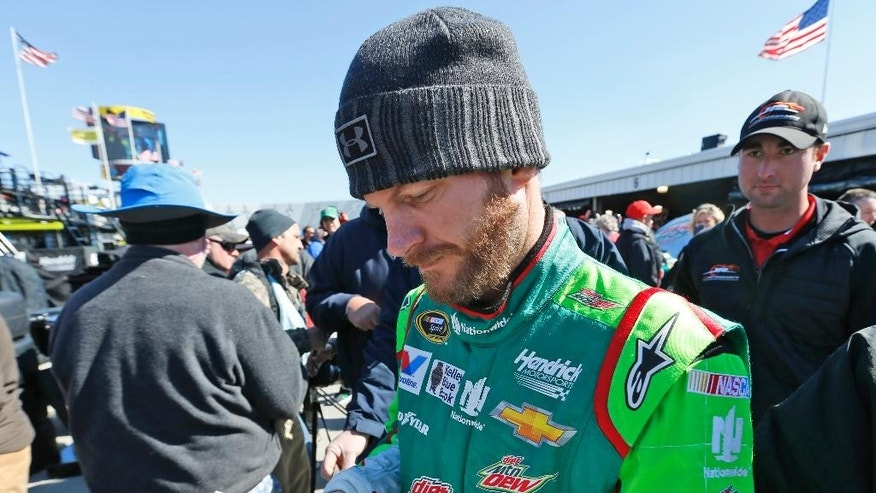 Sprint Cup driver Dale Earnhardt Jr., signs an autograph after practice for Sunday's NASCAR Sprint Cup race at the Martinsville Speedway in Martinsville, Va., Saturday, March 28, 2015.  (AP Photo/Steve Helber)