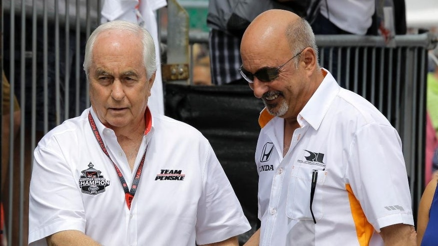 Team owners Roger Penske, left, and Bobby Rahal, shake hands as they walk to pit road before practice for the IndyCar Firestone Grand Prix of St. Petersburg auto race Friday, March 27, 2015, in St. Petersburg, Fla. The race takes place on Sunday. (AP Photo/Chris O'Meara)