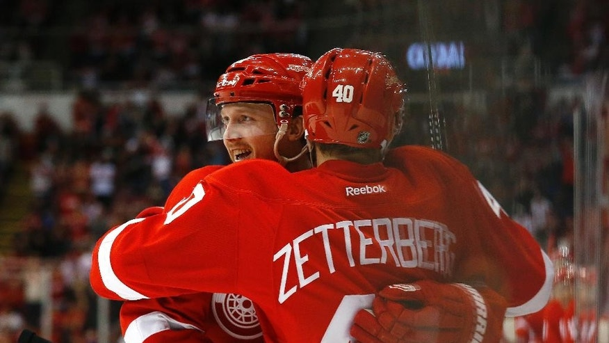 Detroit Red Wings center Gustav Nyquist, left, celebrates his goal against the Tampa Bay Lightning with Henrik Zetterberg in the second period of an NHL hockey game in Detroit, Saturday, March 28, 2015. (AP Photo/Paul Sancya)