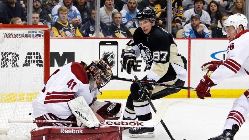 Arizona Coyotes goalie Mike Smith (41) stops a shot by Pittsburgh Penguins' Sidney Crosby (87) with Michael Stone (26) defending during the second period of an NHL hockey game in Pittsburgh Saturday, March 28, 2015. (AP Photo/Gene J. Puskar)