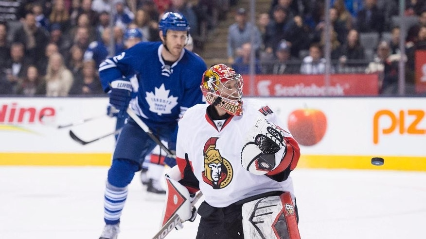 Toronto Maple Leafs defenceman Eric Brewer looks on before his game-winning goal as Ottawa Senators goaltender Craig Anderson looks back at the puck bouncing off the post during overtime in an NHL hockey game in Toronto, Saturday, March 28, 2015. (AP Photo/The Canadian Press, Frank Gunn)