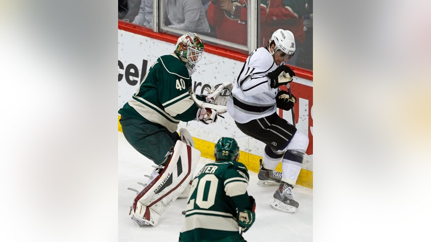 Minnesota Wild goalie Devan Dubnyk, left, joins Los Angeles Kings' Anze Kopitar, right, of Slovenia, in looking for the puck in the first period of an NHL hockey game, Saturday, March 28, 2015, in St. Paul, Minn. (AP Photo/Jim Mone)