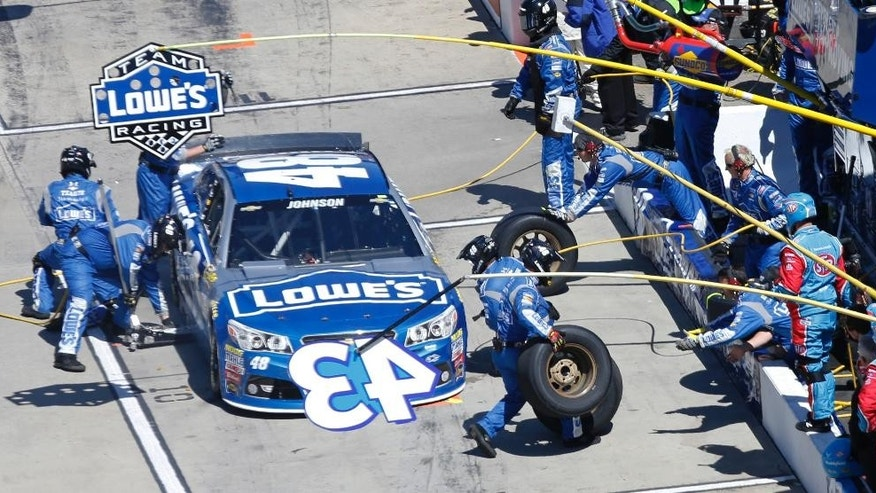 Jimmie Johnson (48) gets service in the pits during the NASCAR Sprint Cup auto race at the Martinsville Speedway in Martinsville, Va., Sunday, March 29, 2015. (AP Photo/Steve Helber)