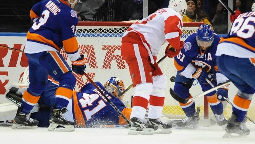 Detroit Red Wings center Pavel Datsyuk (13) shoots the puck past a diving New York Islanders goalie Jaroslav Halak (41) to score as Islanders defenseman Travis Hamonic (3) and center Frans Nielsen (51) try to defend during the second period of an NHL hockey game Sunday, March 29, 2015, in Uniondale, N.Y. (AP Photo/Kathy Kmonicek)