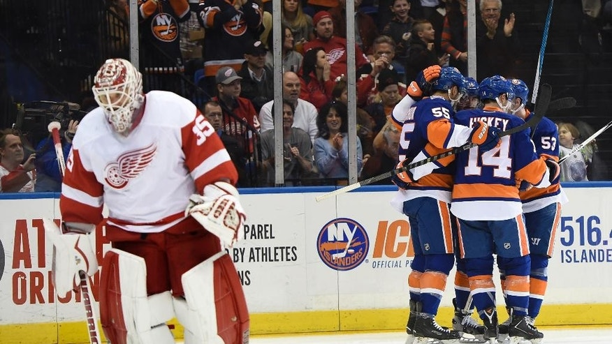 New York Islanders defenseman Johnny Boychuk (55), defenseman Johnny Boychuk (14), center Casey Cizikas (53) and right wing Cal Clutterbuck (15) celebrate Clutterbuck's goal as Detroit Red Wings goalie Jimmy Howard (35) skates away in the second period of an NHL hockey game on Sunday, March 29, 2015, in Uniondale, N.Y. (AP Photo/Kathy Kmonicek)
