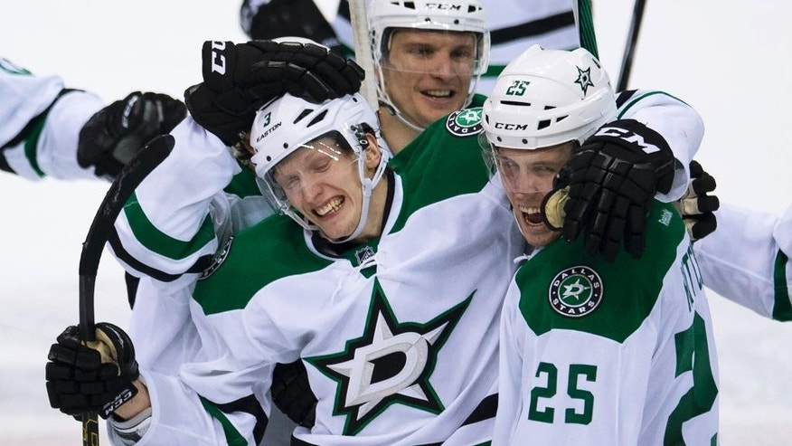 Dallas Stars John Klingberg (3) celebrates his overtime goal against the Vancouver Canucks with teammate Brett Ritchie (25) in an NHL hockey game Saturday, March 28, 2015, in Vancouver, British Columbia. The Stars won 4-3. (AP Photo/The Canadian Press, Jonathan Hayward)