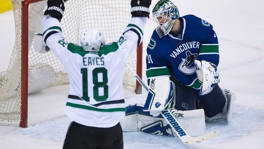 Dallas Stars right wing Patrick Eaves (18) celebrates teammate John Klingberg's goal past Vancouver Canucks goalie Eddie Lack (31) during overtime of an NHL hockey game Saturday, March 28, 2015, in Vancouver, British Columbia. (AP Photo/The Canadian Press, Jonathan Hayward)