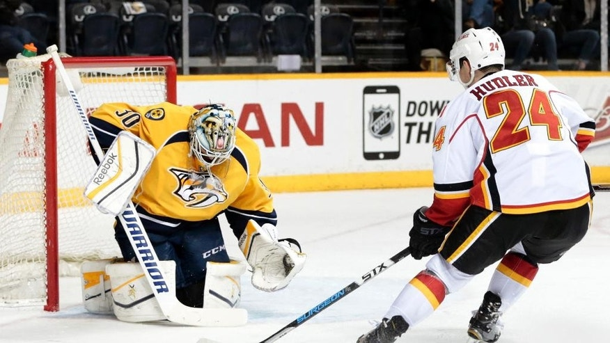 Calgary Flames left wing Jiri Hudler (24), of the Czech Republic, scores a goal against Nashville Predators goalie Carter Hutton (30) in the second period of an NHL hockey game Sunday, March 29, 2015, in Nashville, Tenn. (AP Photo/Mark Humphrey)
