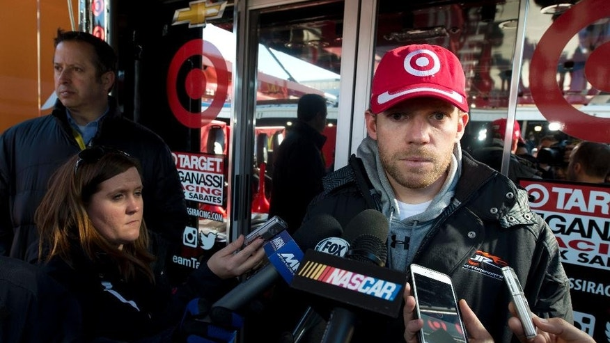 Sprint Cup driver Regan Smith talks to the media outside the hauler of driver Kyle Larson prior to the start of the NASCAR Sprint Cup race at the Martinsville Speedway in Martinsville, Va., Sunday, March 29, 2015. Smith is replacing Larson in the 42 car after Larson failed to get medical clearance after fainting during an autograph session.  (AP Photo/Don Petersen)