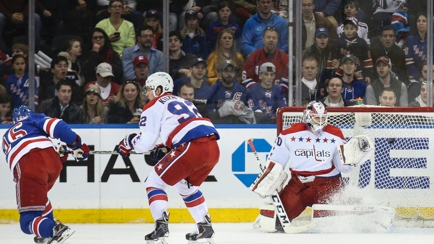 New York Rangers center Derick Brassard (16) scores against Washington Capitals goalie Braden Holtby (70) during the first period of an NHL hockey game, Sunday, March 29, 2015, in New York. (AP Photo/John Minchillo)