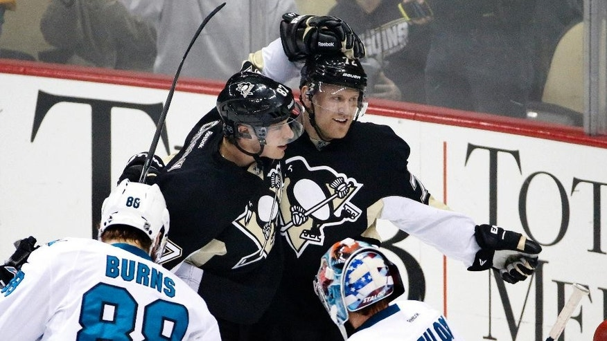 Pittsburgh Penguins' Patric Hornqvist, center, celebrates his goal in the first period with teammate Sidney Crosby (87) during an NHL hockey game against the San Jose Sharks in Pittsburgh on Sunday, March 29, 2015. (AP Photo/Gene J. Puskar)