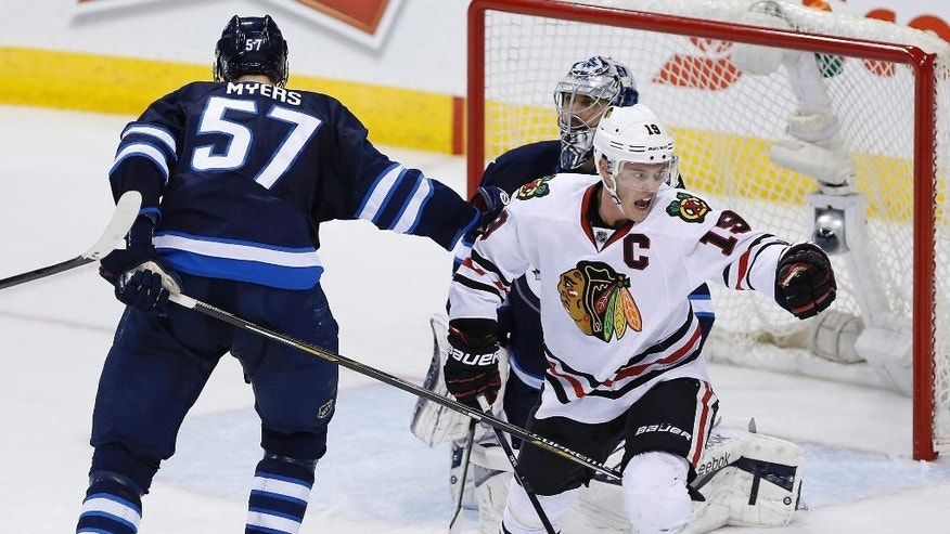 Chicago Blackhawks' Jonathan Toews (19) celebrates his deflection for a goal on Winnipeg Jets goaltender Ondrej Pavelec (31) as Jets' Tyler Myers (57) skates past during the third period of an NHL hockey game Sunday, March 29, 2015, in Winnipeg, Manitoba. (AP Photo/The Canadian Press, John Woods)