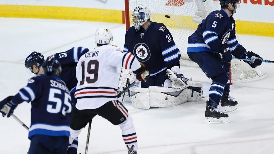 Chicago Blackhawks' Jonathan Toews (19) deflects the shot from the point for a goal on Winnipeg Jets goaltender Ondrej Pavelec (31) as Jets' Mark Scheifele (55), Tyler Myers (57) and Mark Stuart (5) defend during the third period of an NHL hockey game Sunday, March 29, 2015, in Winnipeg, Manitoba. (AP Photo/The Canadian Press, John Woods)