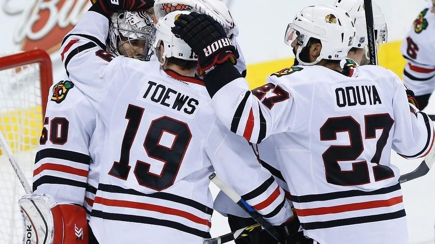 Chicago Blackhawks Jonathan Toews (19) and Johnny Oduya (27) congratulate goaltender Corey Crawford (50) after the win over the Winnipeg Jets in the NHL game in Winnipeg, Mannitoba, on Sunday, March 29, 2015.(AP Photo/The Canadian Press, John Woods)