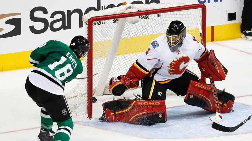 Dallas Stars' Patrick Eaves (18) is unable to score on a shot against Calgary Flames' Jonas Hiller (1) of Switzerland in the third period of an NHL hockey game Monday, March 30, 2015, in Dallas. The Flames won 5-3.  (AP Photo/Tony Gutierrez)