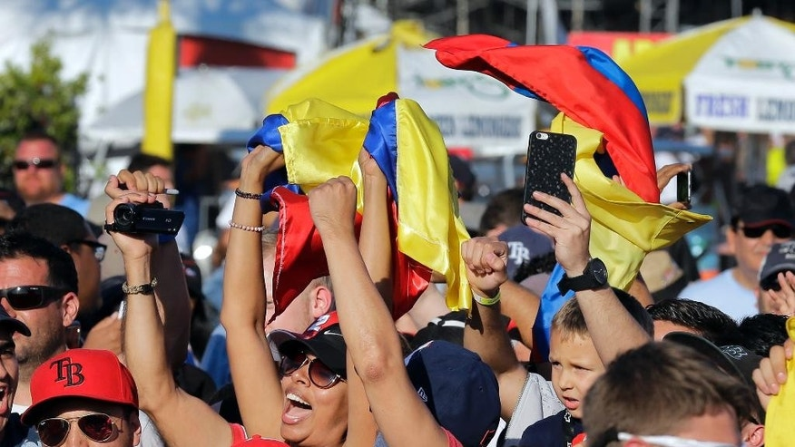 Fans celebrate with Colombian flags after Juan Pablo Montoya, of Colombia, won the IndyCar Firestone Grand Prix of St. Petersburg auto race Sunday, March 29, 2015, in St. Petersburg, Fla.  (AP Photo/Chris O'Meara)