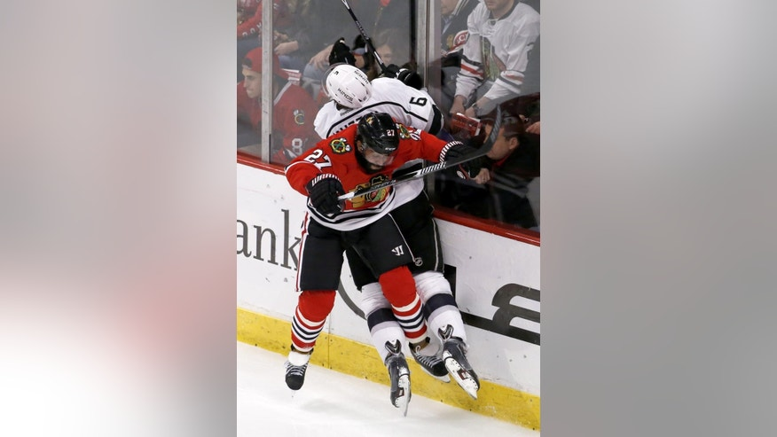 Chicago Blackhawks defenseman Johnny Oduya (27) checks Los Angeles Kings defenseman Jake Muzzin (6) into the boards during the second period of an NHL hockey game Monday, March 30, 2015, in Chicago. (AP Photo/Charles Rex Arbogast)