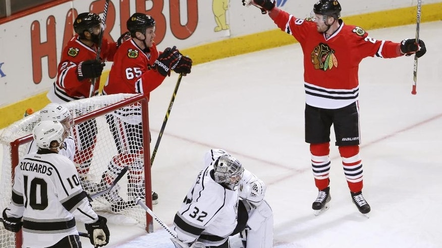 Chicago Blackhawks left wing Bryan Bickell, right, celebrates his goal with teammates Johnny Oduya (27) and Andrew Shaw (65) as Los Angeles Kings goalie Jonathan Quick (32) and Mike Richards (10) watch during the first period of an NHL hockey game Monday, March 30, 2015, in Chicago. (AP Photo/Charles Rex Arbogast)