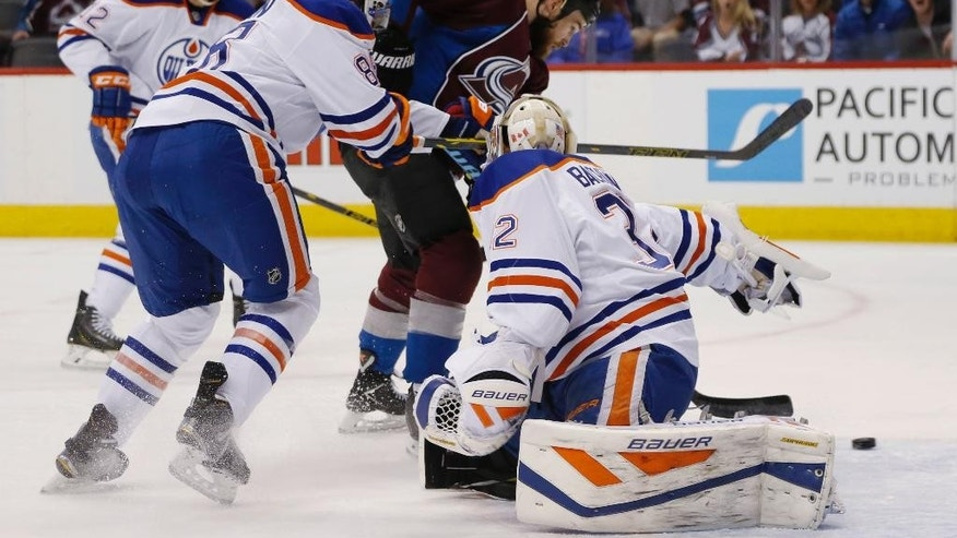Colorado Avalanche center Ryan O'Reilly, center, scores a goal past Edmonton Oilers defenseman Brandon Davidson, left, and goalie Richard Bachman in the first period of an NHL hockey game Monday, March 30, 2015, in Denver. (AP Photo/David Zalubowski)
