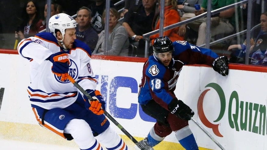 Edmonton Oilers defenseman Nikita Nikitin, left, of Russia, steals the puck from Colorado Avalanche center Joey Hishon in the first period of an NHL hockey game Monday, March 30, 2015, in Denver. (AP Photo/David Zalubowski)