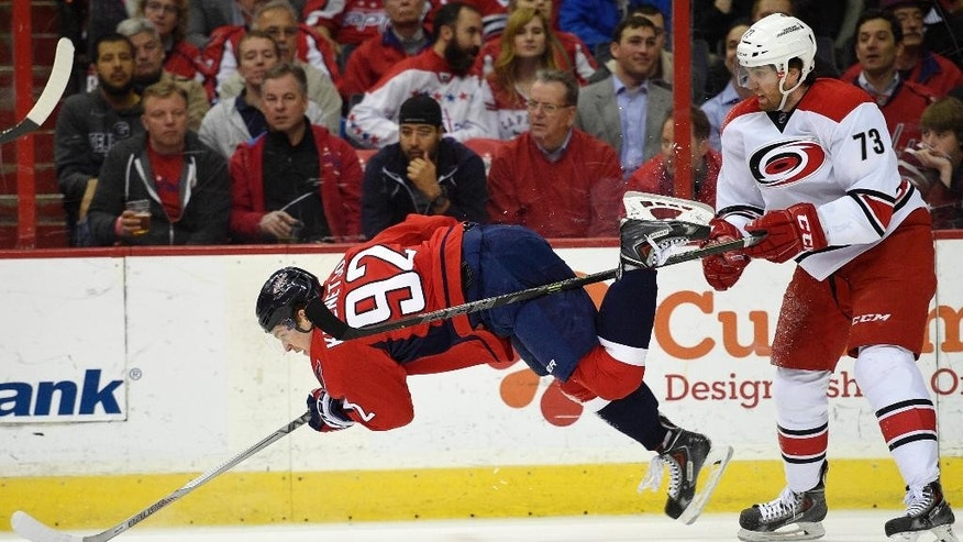 Washington Capitals center Evgeny Kuznetsov (92), of Russia, gets tripped up by Carolina Hurricanes defenseman Brett Bellemore (73) during the first period of an NHL hockey game, Tuesday, March 31, 2015, in Washington. (AP Photo/Nick Wass)