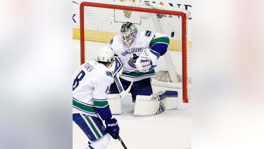 Vancouver Canucks goalie Eddie Lack, of Sweden, fails to block a shot by Nashville Predators' Viktor Stalberg, of Sweden, in the second period of an NHL hockey game Tuesday, March 31, 2015, in Nashville, Tenn. At left is Canucks defenseman Chris Tanev (8). (AP Photo/Mark Humphrey)